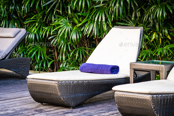 Beautiful outdoor swimming pool with bed deck chair and umbrella