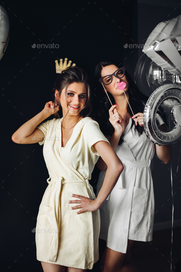 Two young ladies holding accessories and posing at camera - Stock Photo - Images