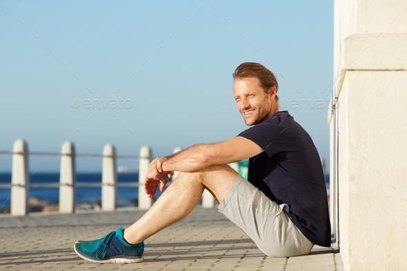 active middle age man sitting outside and smiling - Stock Photo - Images