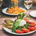 Italian dinner at bistrot with caprese and pasta, square crop - PhotoDune Item for Sale