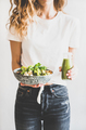 Woman holding vegan superbowl and green smoothie in hands - PhotoDune Item for Sale