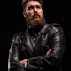 Portrait of Handsome bearded man wearing a leather jacket with serious expresion over black - PhotoDune Item for Sale