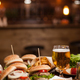 Tasty different burgers and a glass of cold beer on wooden table - PhotoDune Item for Sale