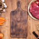 Top view of vintage cutting board next to two pieces of red meat on wooden table - PhotoDune Item for Sale