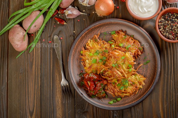 Top view at flat lay potato pancakes in clay dish with sun-dried - Stock Photo - Images
