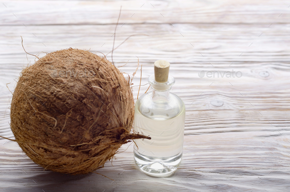 Coconut and oil in glass jar on white wooden table. Care concept - Stock Photo - Images