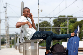 Male traveler at railway station using cellphone