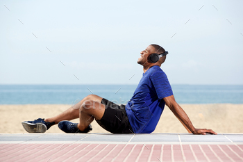 African male runner enjoying music at the beach