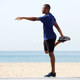 Fit young african man doing warm up exercise on beach - PhotoDune Item for Sale