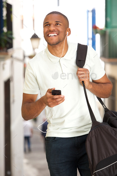 young african american male traveler walking and listening music with mobile phone