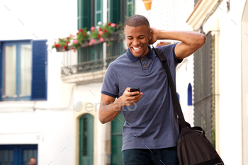 Young african man walking outdoors with mobile phone