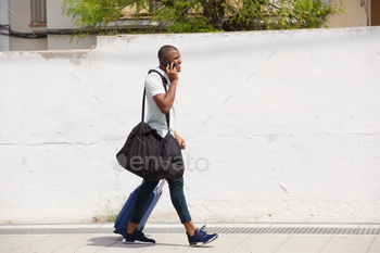 African american male traveler walking outside and talking on cell phone
