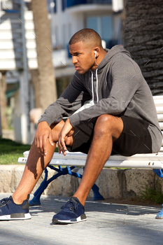 African american male runner sitting outdoors on bench