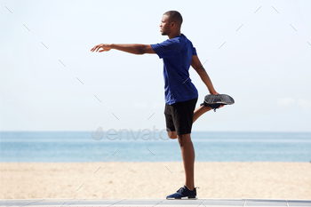 Fit young african man doing warm up exercise on beach