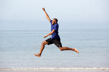 Portrait of excited young african guy running and jumping along the sea