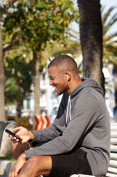 Portrait of young african male runner listening music on smart phone