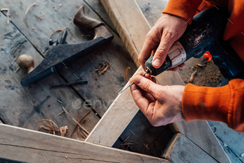 worker changes a drill in a screwdriver, against the background of a wooden table