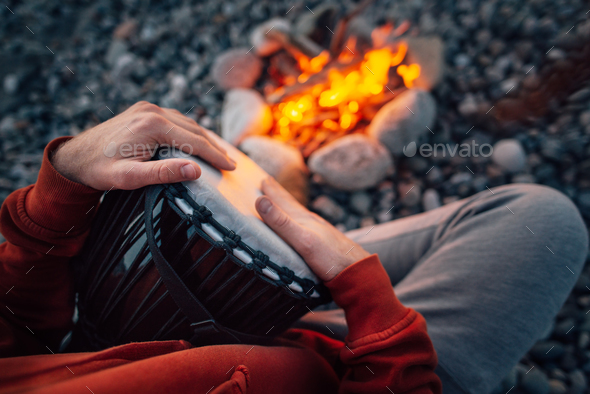 percussionist playing djembe sitting by fire, close-up - Stock Photo - Images
