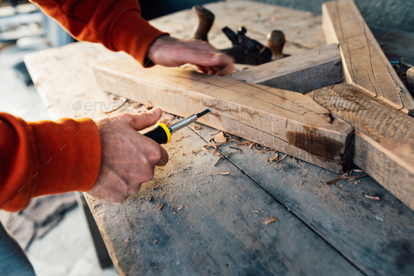worker screw up  wooden rail with a screw with a screwdriver, on table in sawdust - Stock Photo - Images