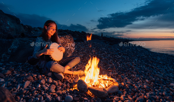 cheerful percussionist girl playing djembe sitting on beach by t - Stock Photo - Images