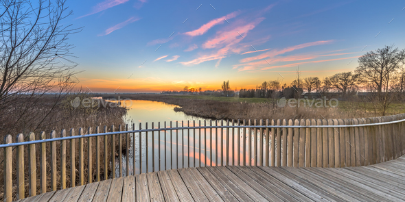 Wooden deck balustrade sunset over swamp - Stock Photo - Images