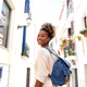 Smiling african female walking on the narrow street with bag - PhotoDune Item for Sale