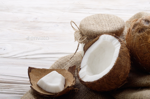 Coconut shell with meat on hemp sackcloth on white wooden kitche - Stock Photo - Images