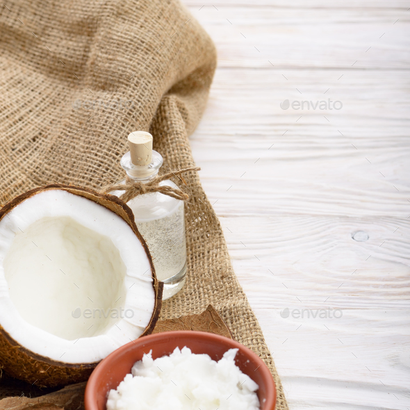 Coconut oil in brown clay bowl, glass bottle, coconut shell with - Stock Photo - Images