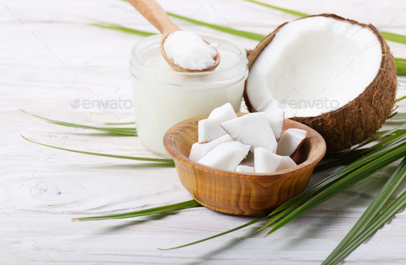 Coconut shell hard oil in glass jar and coconut meat pieces in b - Stock Photo - Images