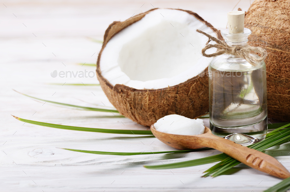 Coconut shell pieces and palm leaves on white wooden table - Stock Photo - Images