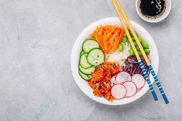 Salmon poke bowl with rice, radish,cucumber, carrots, edamame, red cabbage and sesame seeds. - Stock Photo - Images