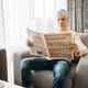 Adult man sitting on couch and reading newspaper - PhotoDune Item for Sale