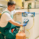 Worker in uniform fills compressor of refrigerator - PhotoDune Item for Sale