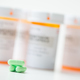 Green capsules in front of orange pharmacy bottles - PhotoDune Item for Sale