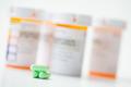 Green capsules in front of orange pharmacy bottles - PhotoDune Item for Sale