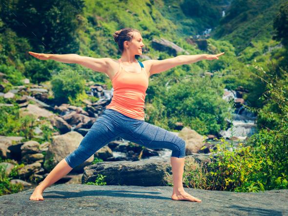 Woman doing Ashtanga Vinyasa Yoga Virabhadrasana 2 Warrior pose - Stock Photo - Images