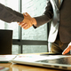 Two businessmen join hands after reaching a business agreement. - PhotoDune Item for Sale