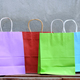 Multi-colored shopping bags placed on a wooden table. - PhotoDune Item for Sale