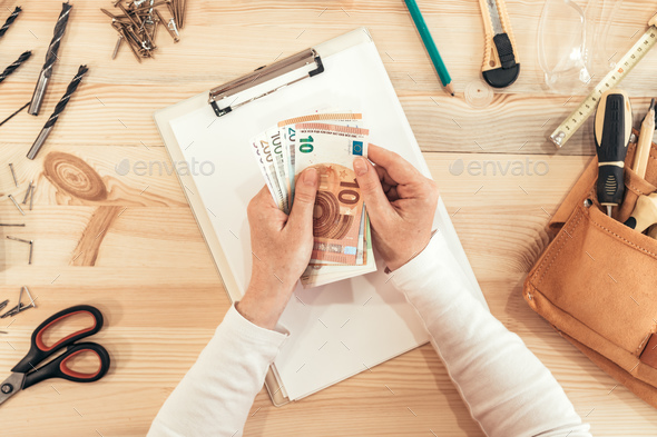 Female carpenter counting money, top view - Stock Photo - Images