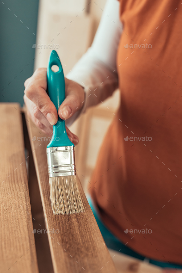 Female carpenter varnishing wooden crate with brush - Stock Photo - Images