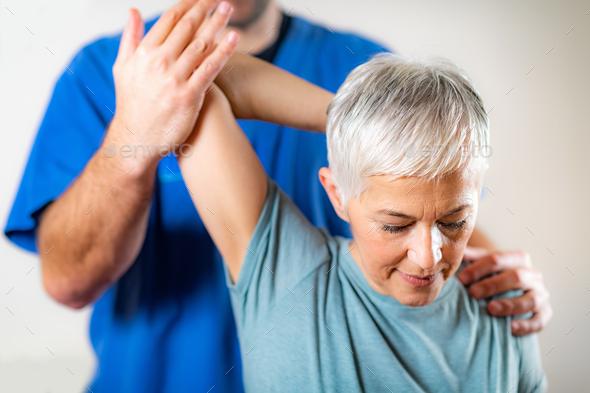 Therapist Checking Senior Woman's Arm - Stock Photo - Images