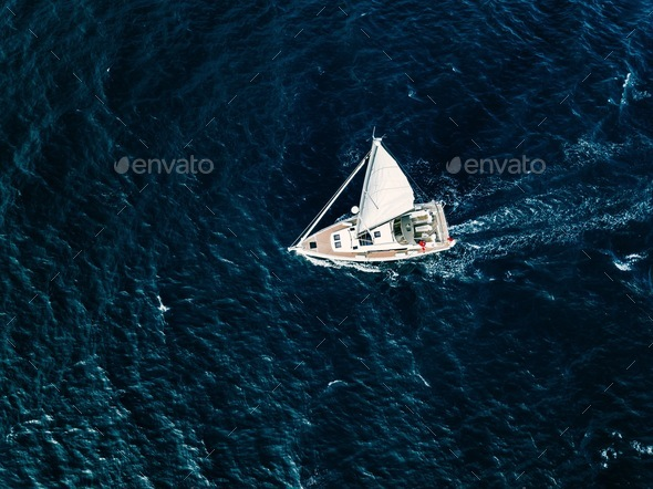 Aerial view of Sailing ship yachts with white sails  in deep blue sea - Stock Photo - Images