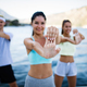 Fit group of happy people exercising outdoor. Smiling friends doing fitness workout - PhotoDune Item for Sale