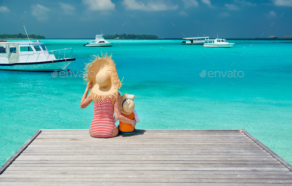 Toddler boy with mother sitting on wooden jetty - Stock Photo - Images