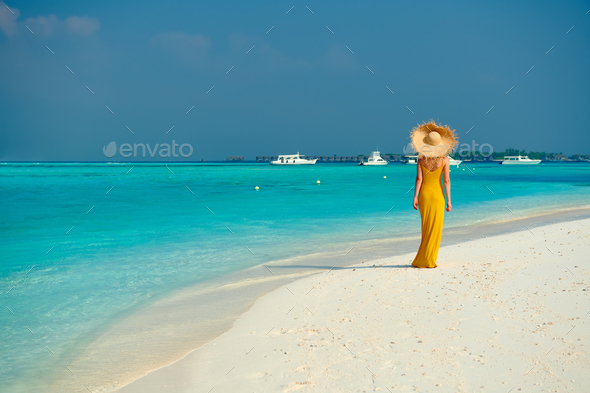 Woman in dress walking on tropical beach - Stock Photo - Images