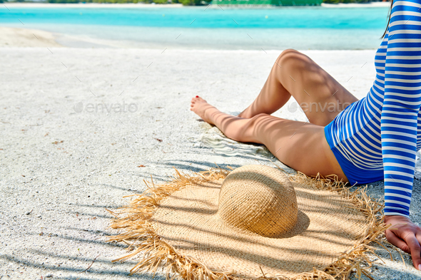 Woman sitting on beach under palm tree - Stock Photo - Images