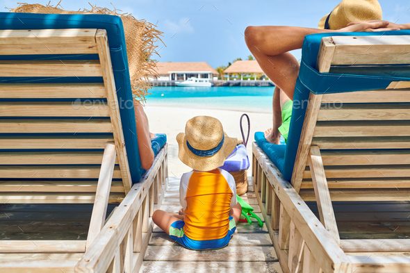 Family at beach on wooden sun bed loungers - Stock Photo - Images