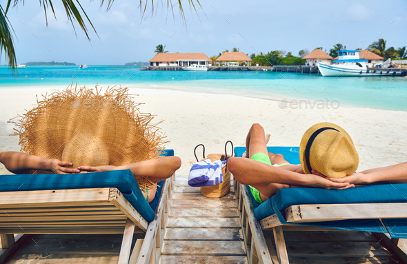 Couple at beach on wooden sun bed loungers - Stock Photo - Images