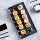 Various Fresh and delicious sushi set on black slate with metal and slate sticks, sauce on light - PhotoDune Item for Sale