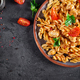 Pasta Fusilli  with tomatoes, chicken meat and parsley on plate on dark table. Top view. Flat lay - PhotoDune Item for Sale